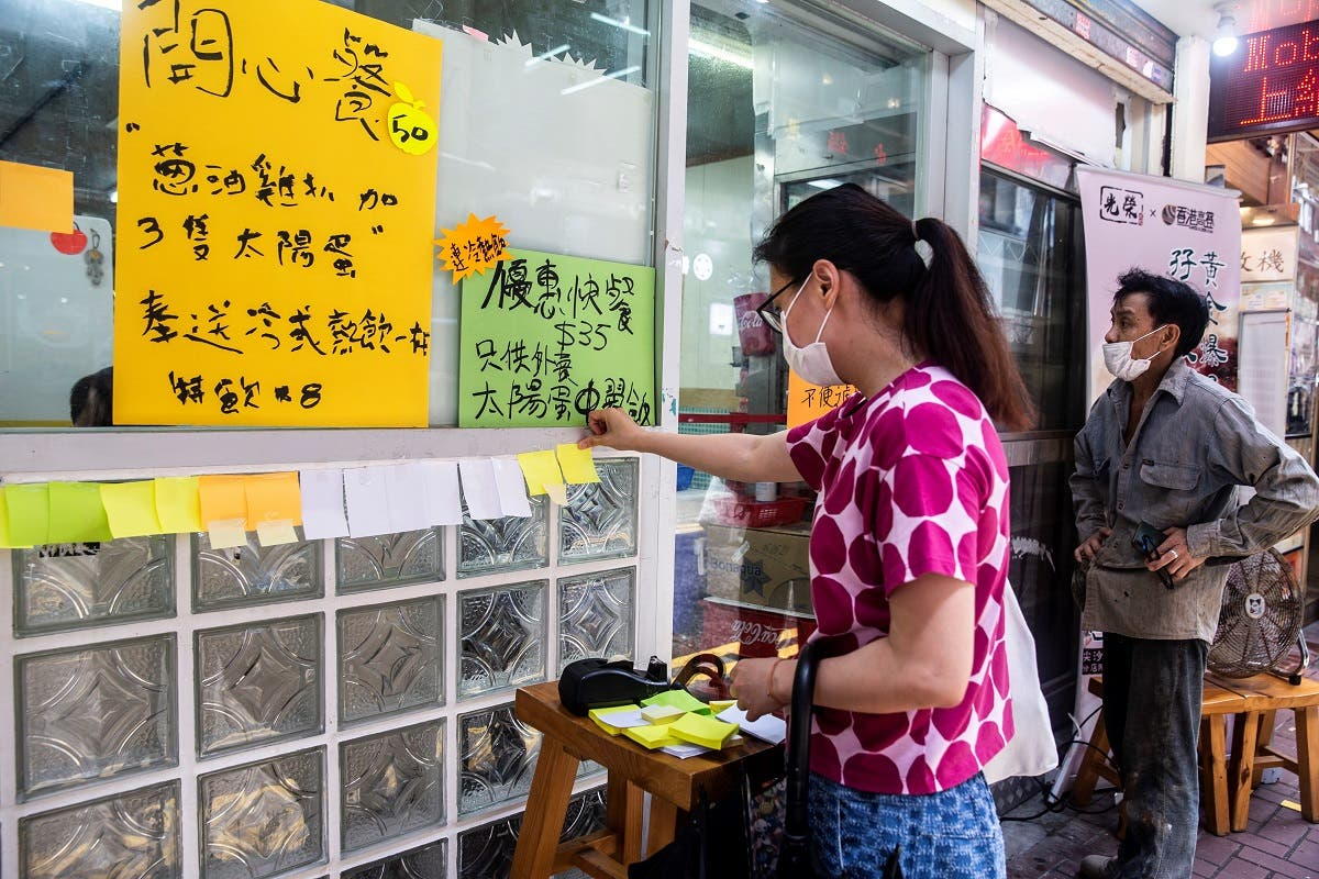 """A woman (L) sticks a blank note onto a """"Lennon Wall"""" outside a pro-democracy restaurant in Hong Kong on July 3, 2020, in response to the new national security law. (AFP)"""