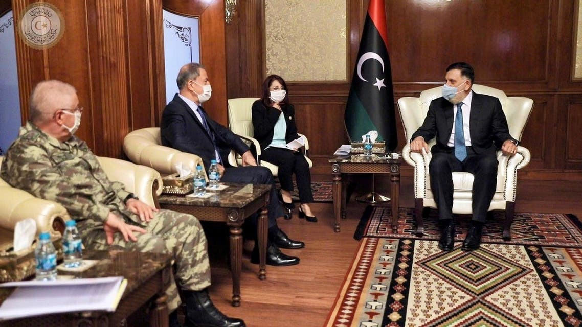 Fayez al-Sarraj wears a protective mask as he meets with Turkish Minister of Defense Hulusi Akar in Tripoli. (Reuters)