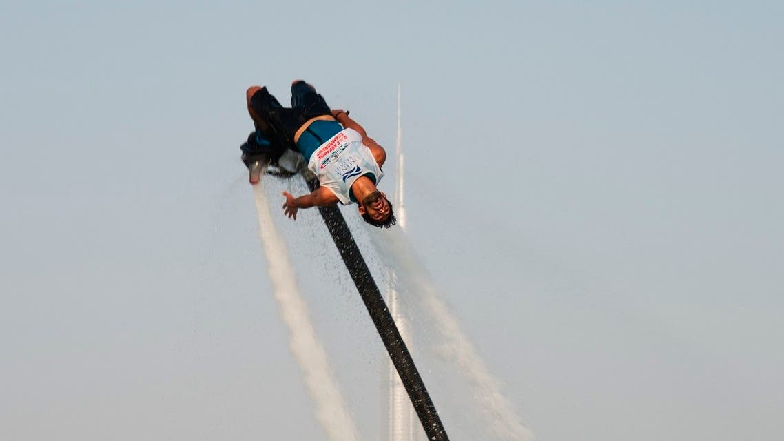 A man rides a flyboard with the Burj Khalifa, the world's tallest building, in the distance in Dubai, United Arab Emirates, Thursday, June 25, 2020. (AP)