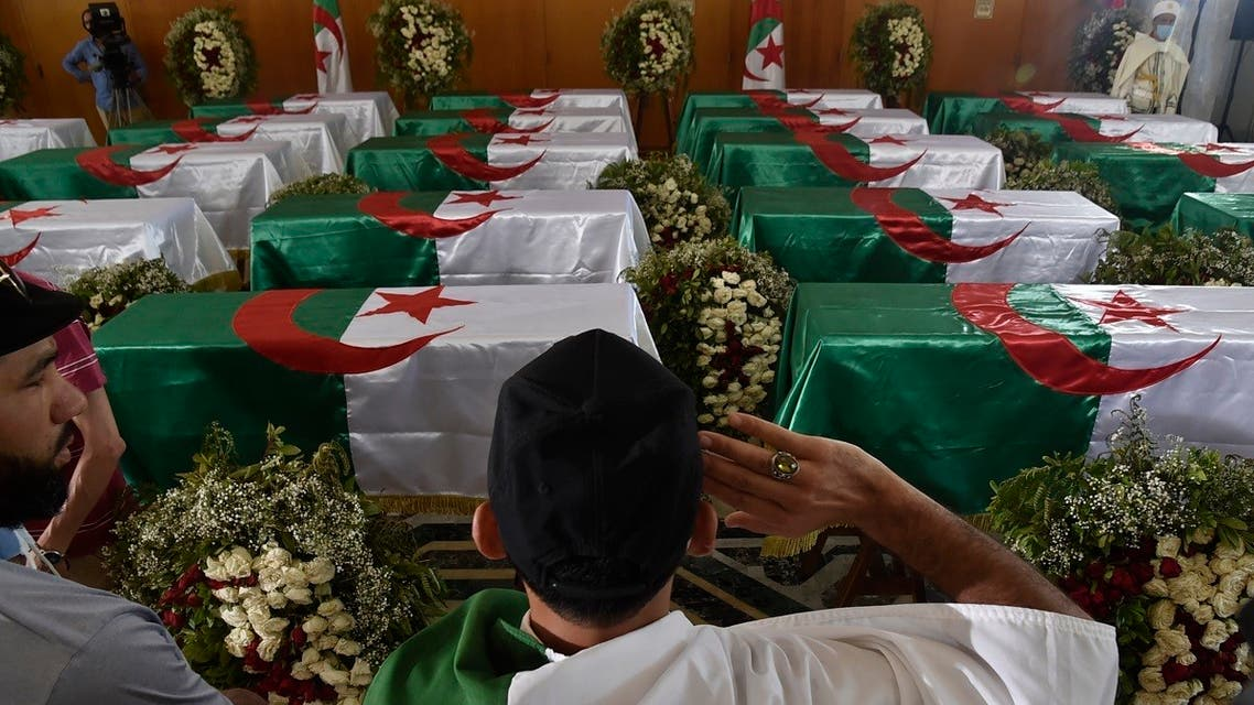 An Algerian man pays respect in front of the national flag-draped coffins containing the remains of 24 Algerian resistance fighters decapitated during the French colonial conquest of the North African country, presented at the capital's Palais De La Culture Moufdi Zakaria on July 4, 2020, a day after they were flown in from France. (AFP)