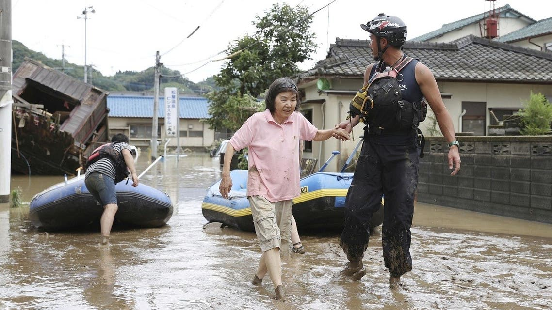 A rescue worker helps local residents at a flooded area caused by a heavy rain along Kuma River in Hitoyoshi, Kumamoto prefecture, southern Japan. (Kyodo/via Reuters)