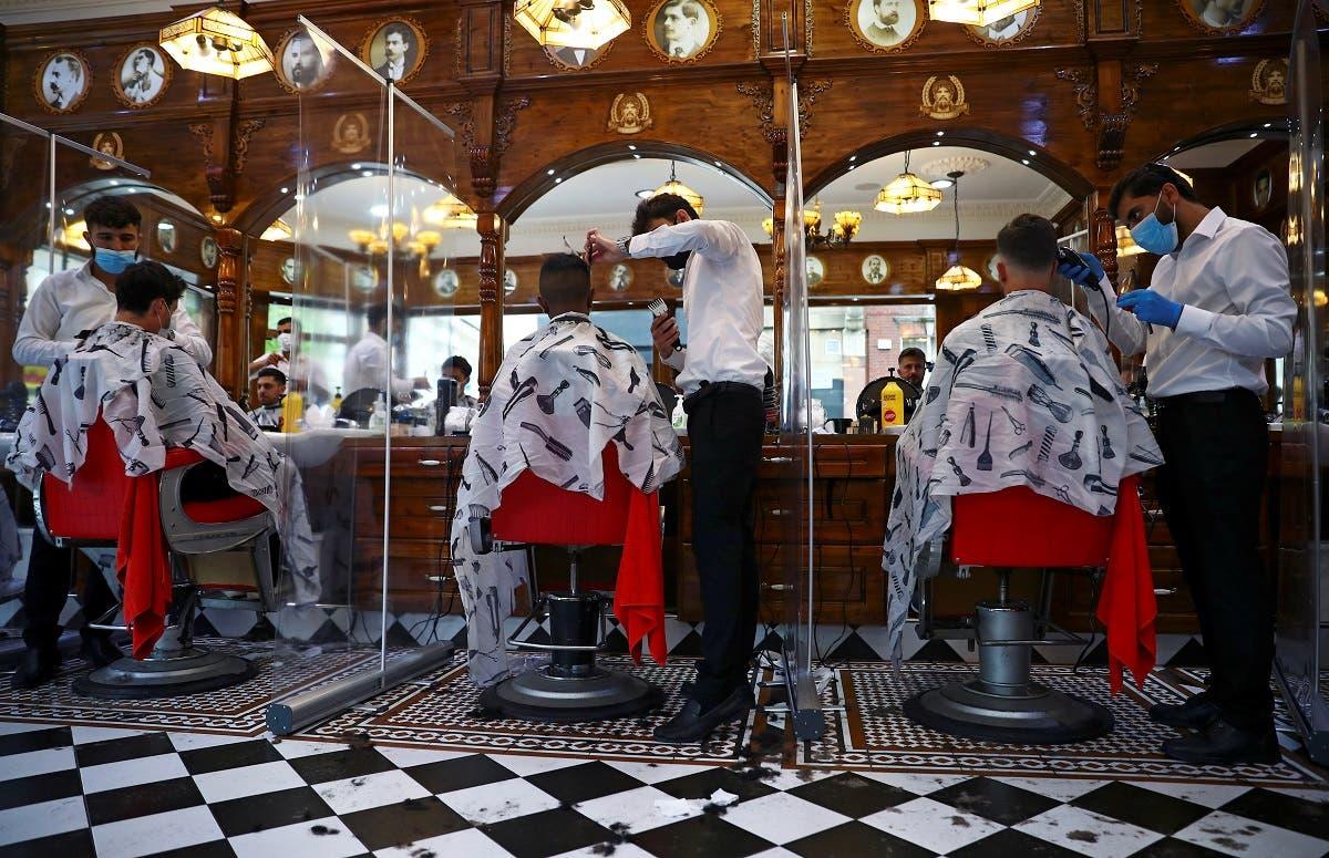 Men have their hair cut at Savvas Barbers as it reopened following the outbreak of the coronavirus disease (COVID-19), in London, Britain. (Reuters)