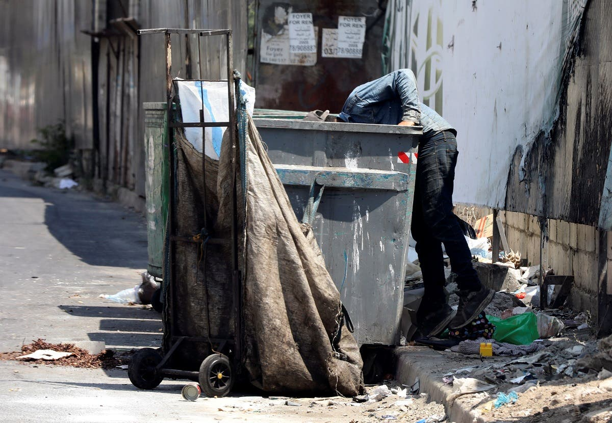 A man searches through a garbage bin in Beirut, Lebanon, June 30, 2020. (Reuters)
