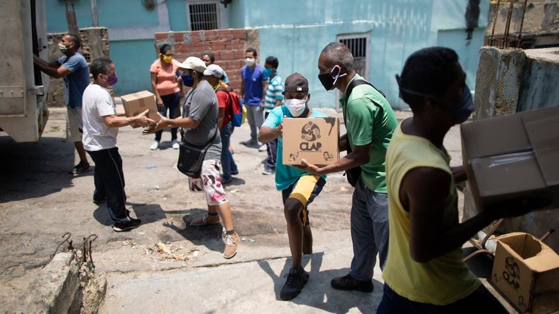 Residents help to unload boxes of basic food staples, such as pasta, sugar and flour, provided by a government food assistance program, in Caracas' slum of Petare, Venezuela, Thursday, April 30, 2020. (AP)