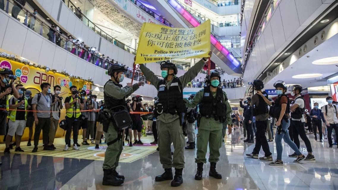 شرطة مكافحة الشغب ترفع تحذيرا خلال مظاهرة في مركز تجاري في هونغ كونغ في 6 يوليو 2020 ، ردًا على قانون الأمن القومي الجديد