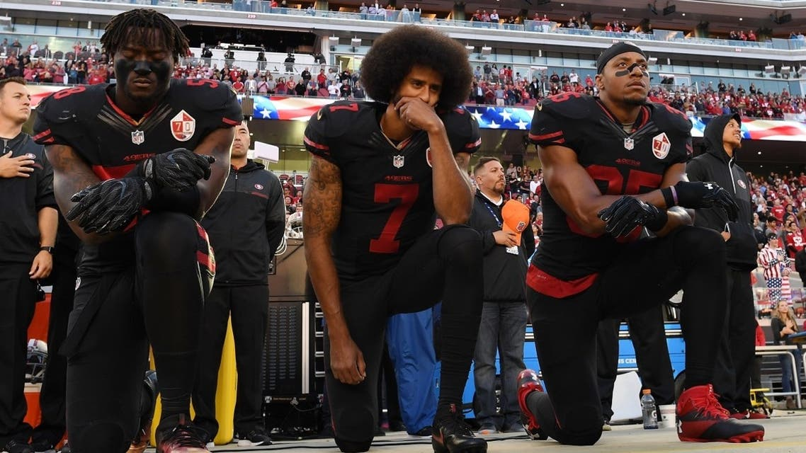 (L-R) Eli Harold #58, Colin Kaepernick #7, and Eric Reid #35 of the San Francisco 49ers kneel in protest during the national anthem prior to their NFL game against the Arizona Cardinals at Levi's Stadium on October 6, 2016 in Santa Clara, California. (AFP)