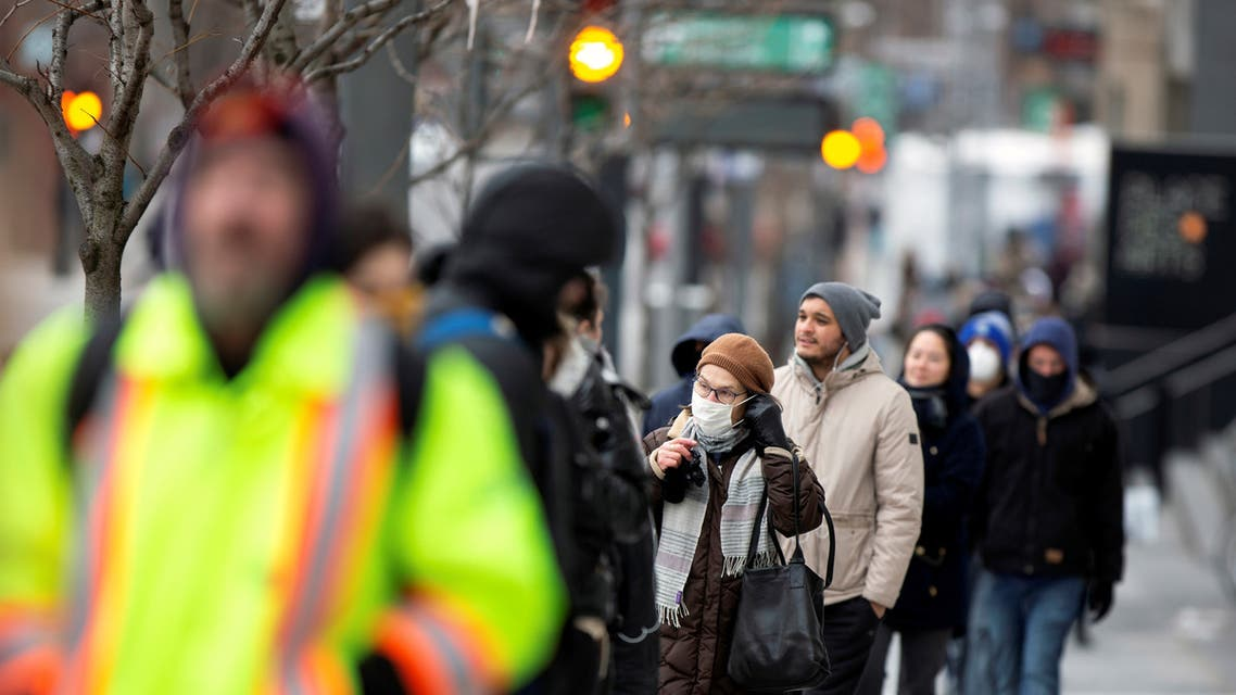 A woman adjusts her mask while she waits in line as the city's public health unit holds a walk-in clinic testing for coronavirus disease (COVID-19) in Montreal. (Reuters)
