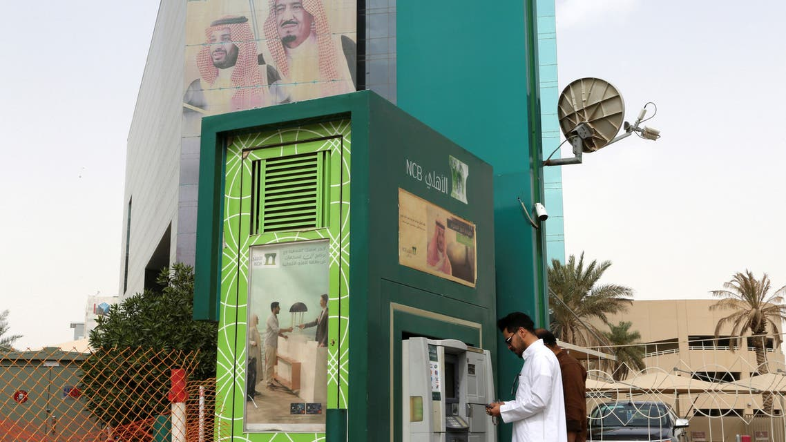 A man withdraws money from an ATM outside the Saudi NCB bank, after an outbreak of coronavirus, in Riyadh. (Reuters)