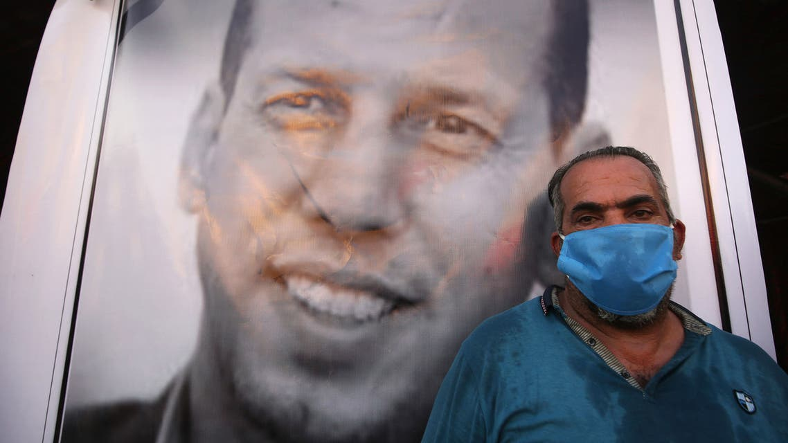 An Iraqi demonstrator wearing a face mask to protect agaisnt the Covid-19 coronavirus, attends a symbolic funeral for slain Iraqi jihadism expert Hisham al-Hashemi. (AFP)