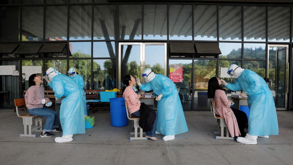 Medical workers collect swabs from high school teachers for nucleic acid tests at a school in Yichang. (Reuters)