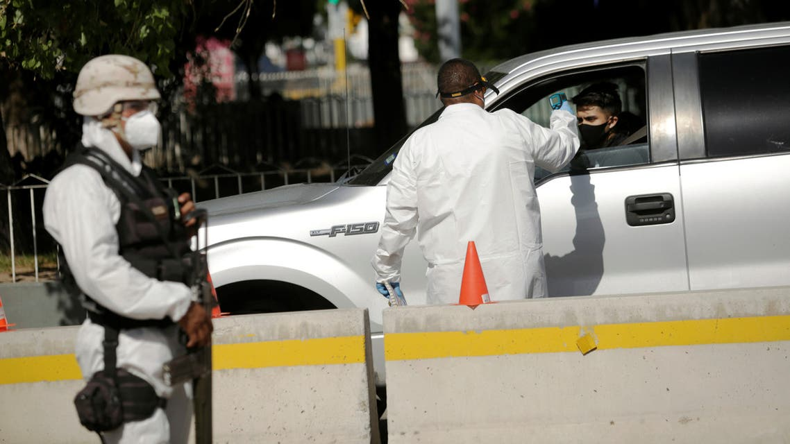 Mexican paramedic checks the temperature of a traveler as he enters to Ciudad Jurez, Mexico from the United States through the Stanton-Lerdo international bridge to prevent contagion due to the coronavirus disease (COVID-19) in Ciudad Juarez , Mexico July 4, 2020. REUTERS/Jose Luis Gonzalez