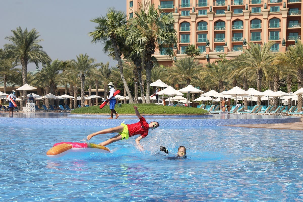 Children play at a swimming pool in the Atlantis The Palm hotel, as the Emirates reopen to tourism amid coronavirus disease (COVID-19), in Dubai. (Reuters)