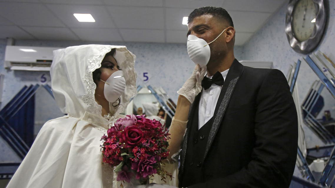 Newly-wed Palestinians Eshaq Musleh (R) and Shayma Titi, both wearing protective masks during the COVID-19 coronavirus pandemic. (AFP)