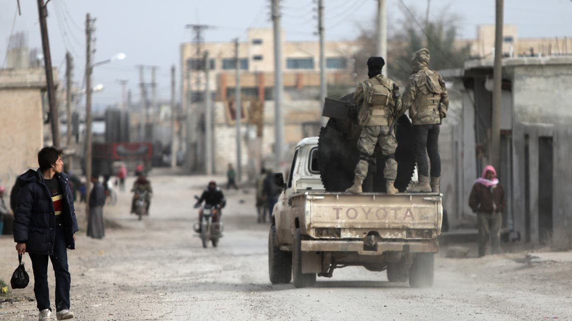 Turkish-backed Syrian fighters ride in the back of a truck fitted with an anti-aircraft gun as they patrol along a street in the northern Syrian town of Tal Abyad by the border with Turkey on February 4, 2020.