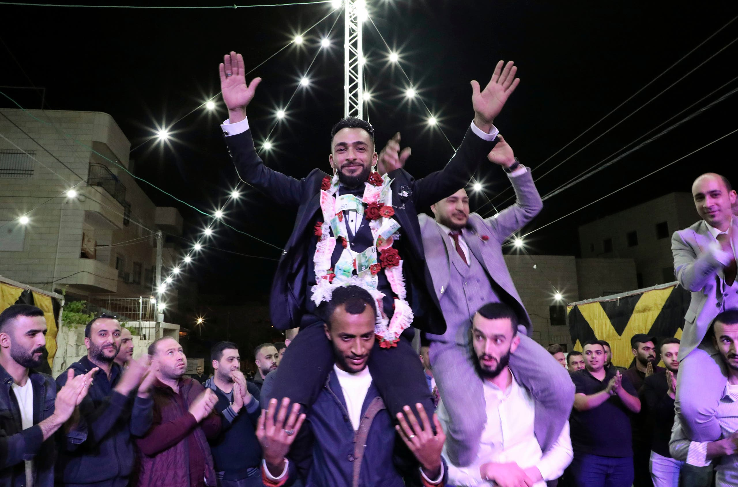 Palestinian groom Basel Abu al-Halawa celebrates with friends and family during a belated wedding party in front of his house in the West Bank city of Hebron. (AFP)