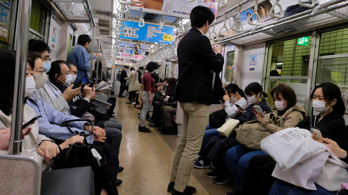Commuters wearing face masks travel on a subway train in Tokyo on May 7, 2020.