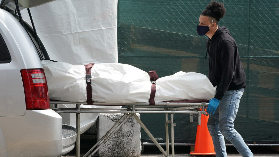 (FILES) In this file photo taken on April 8, 2020, a body is moved from a refrigeration truck serving as a temporary morgue to a vehicle at the Brooklyn Hospital Center, in the Borough of Brooklyn in New York. The United States passed another grim coronavirus milestone on July 6, 2020 as the death toll from the virus climbed past 130,000, according to a tally kept by Johns Hopkins University.