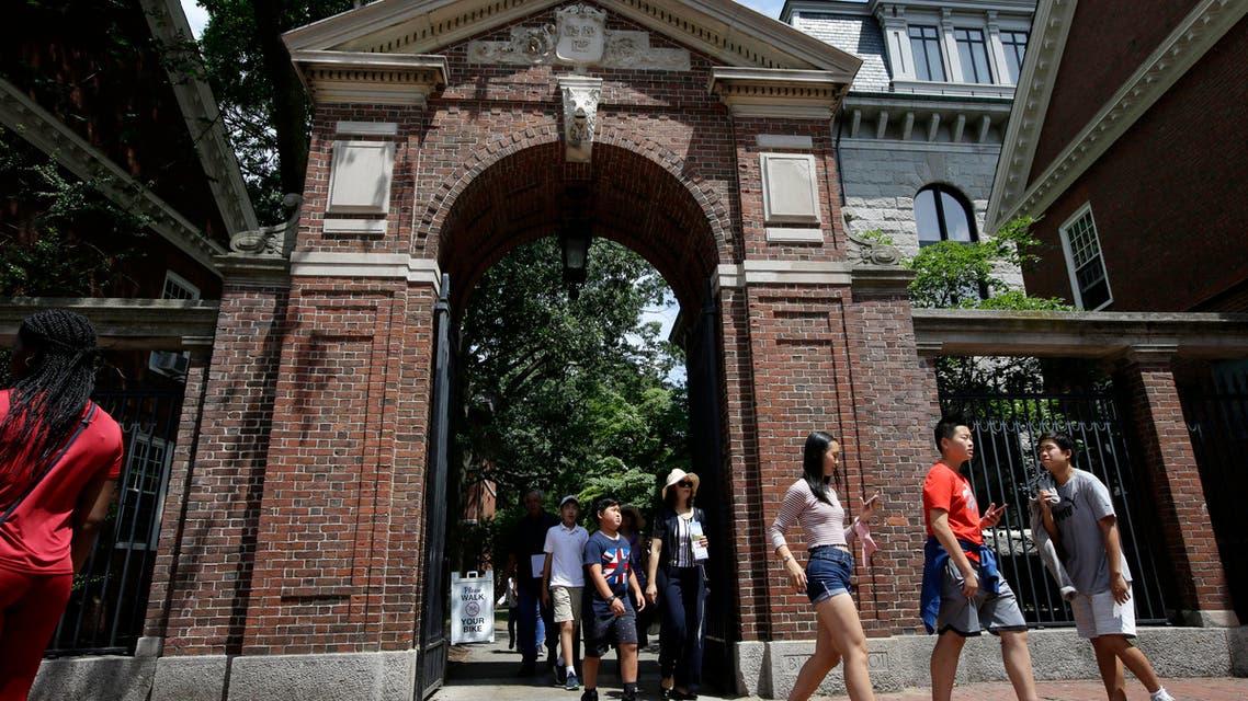people walk through a gate as they depart Harvard Yard, at Harvard University, in Cambridge, Mass. (AP)