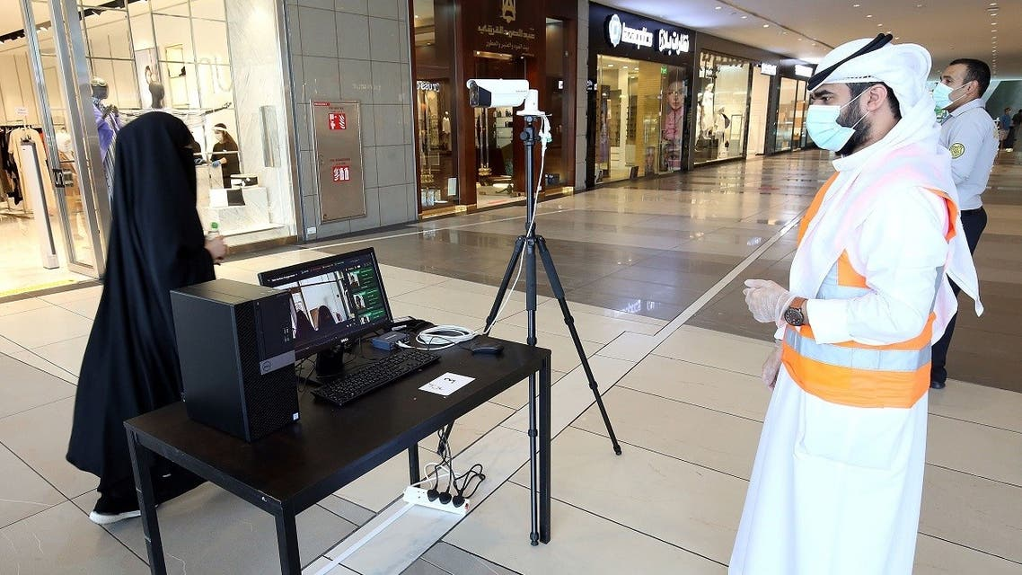 Kuwaiti security check a visitor's temperature at the entrance of the re-opened Avenues Mall, the country's largest shopping centre, on June 30, 2020 in Kuwait City. (AFP)