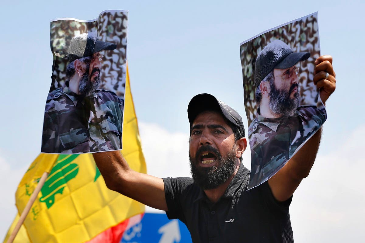 A Hezbollah supporter holds posters of Hezbollah military commander Imad Mughniyeh, while protesting the visit to Lebanon by US Gen. Kenneth McKenzie, July 8, 2020. (AP)