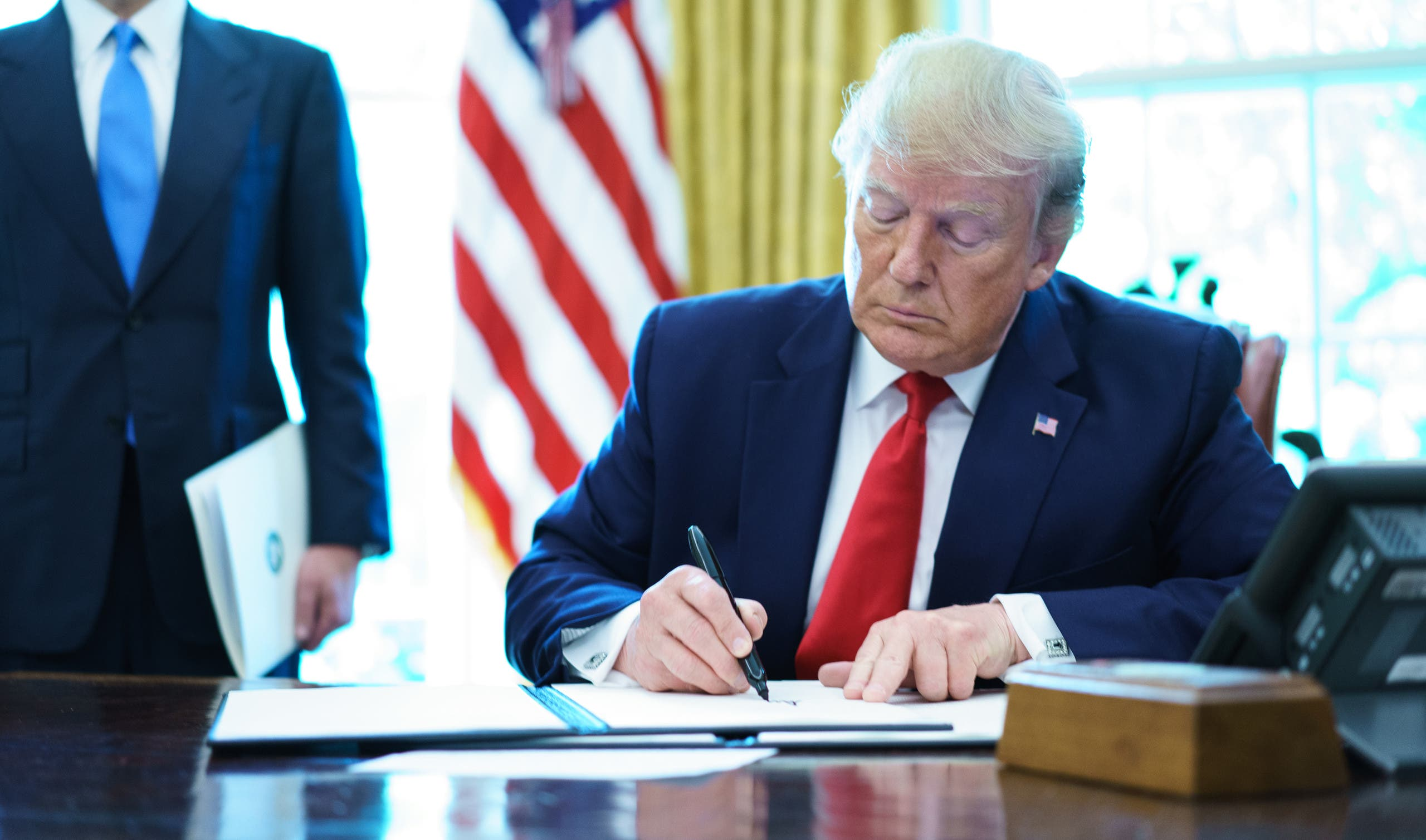 US President Donald Trump signs an executive order on Iran sanctions in the Oval Office of the White House on June 24, 2019. (AFP)