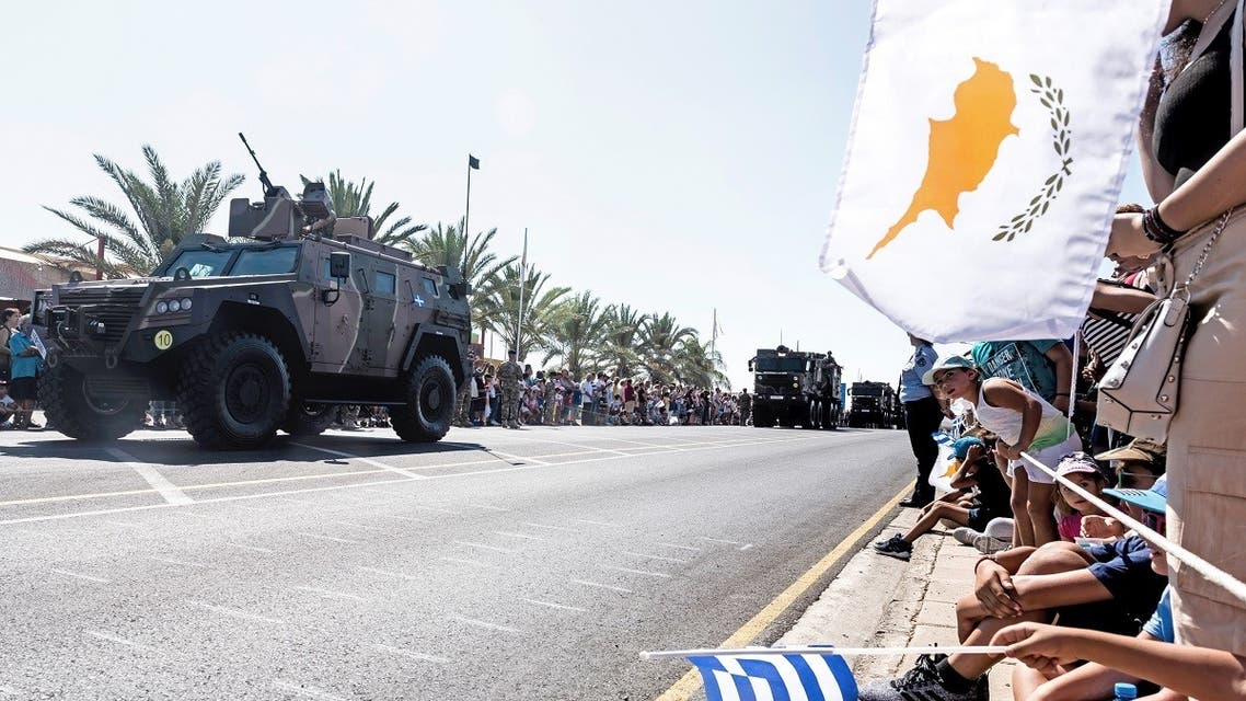 In this file photo taken on October 1, 2019 Greek (C) and Cypriot (R) national flags wave as military trucks takes part in a military parade marking the 59th anniversary of Cyprus' independence from British colonial rule, in the capital Nicosia. (AFP)