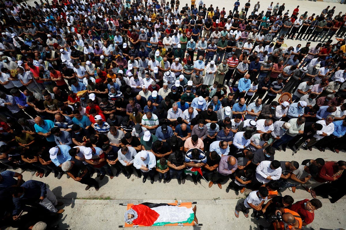 Mourners pray before the body of Palestinian man Ibraheem Yakoub during his funeral in Kifl Haris in the Israeli-occupied West Bank on July 10, 2020. (Reuters)