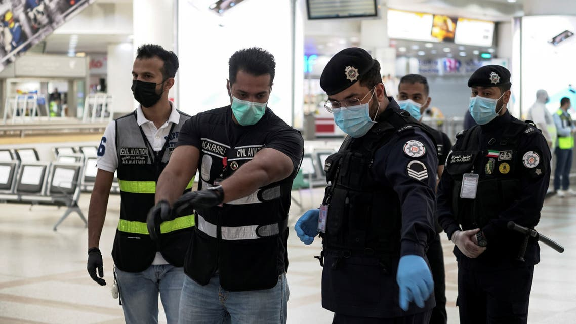 Police and civil aviation personnel wearing protective face masks work at the Kuwait Airport following the outbreak of the coronavirus. (Reuters)
