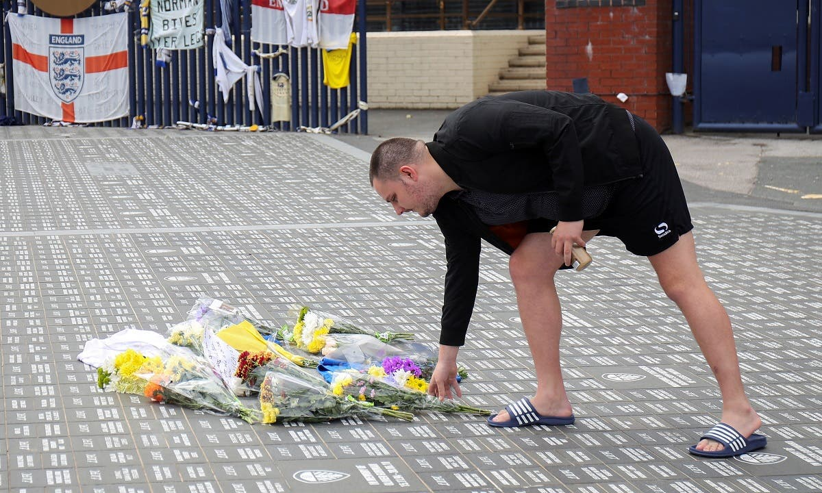 A man lays flowers on the ground in memory of Jack Charlton at Leeds United Stadium Elland Road, in Leeds, Britain, on July 11, 2020. (Reuters)