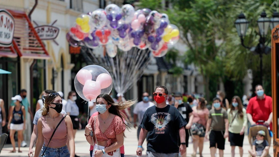 guests required to wear masks because of the coronavirus stroll through the Disney Springs shopping, dining and entertainment complex in Lake Buena Vista, Flaorida. (AP)