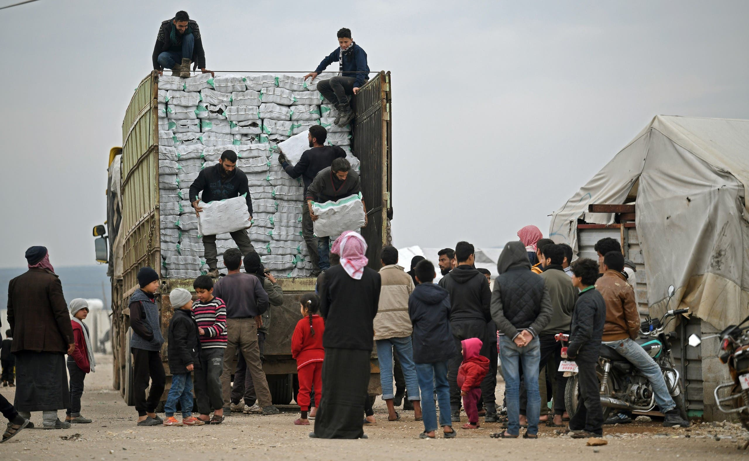 Displaced Syrians queue to receive humanitarian aid, consisting of heating material and drinking water, at a camp in the town of Mehmediye, near the town of Deir al-Ballut along the border with Turkey, on February 21, 2020.