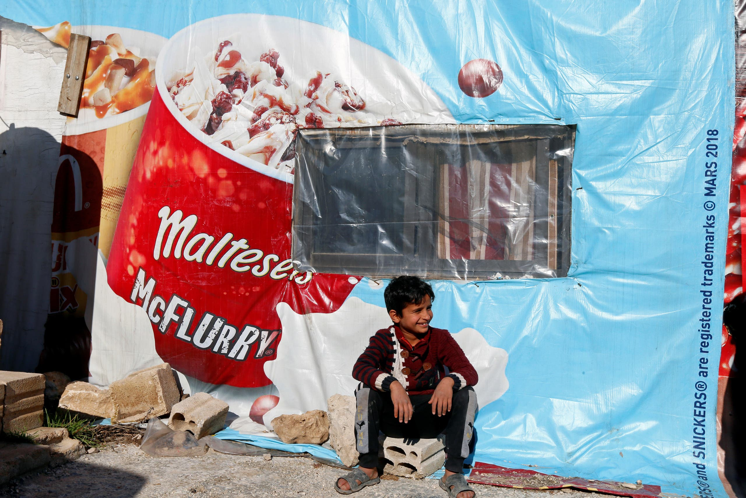 A Syrian refugee boy sits outside a tent at a camp in Bar Elias, in the Bekaa Valley, Lebanon January 13, 2020. Picture taken January 13, 2020. (Reuters)