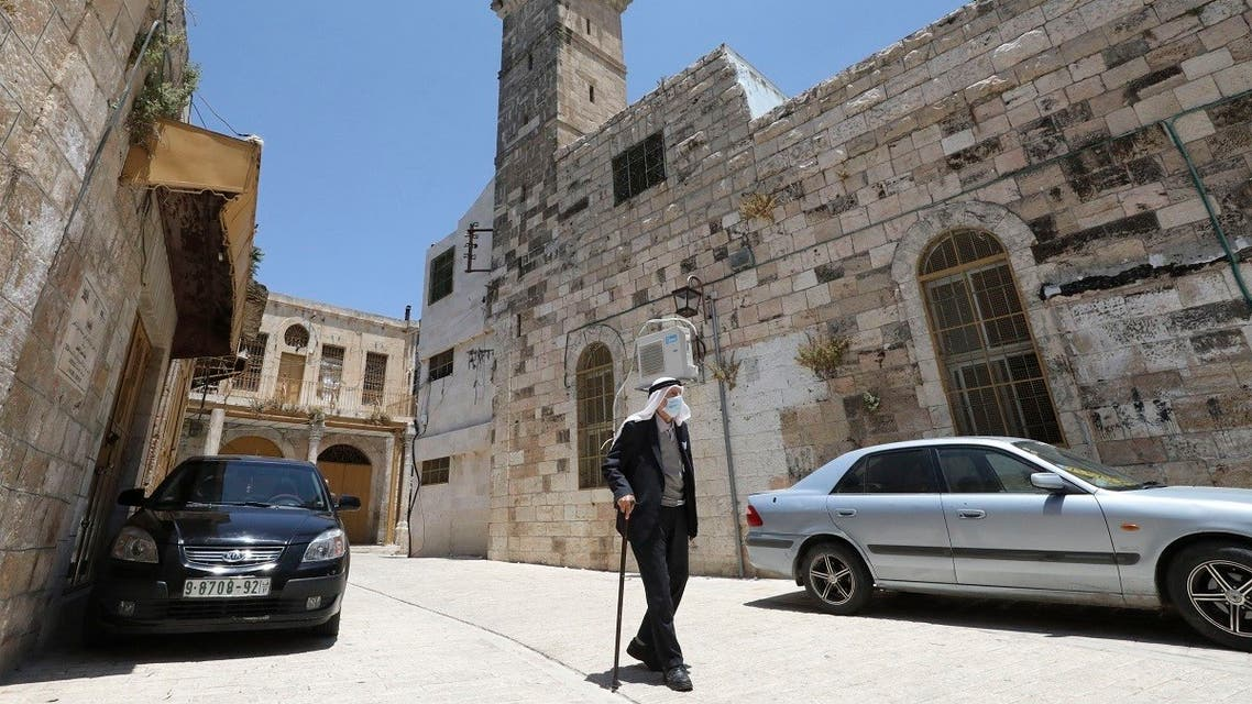 A Palestinian man wearing a protective face mask walks past the closed al-Qazazin mosque in the Old City of the West Bank town of Hebron. (AFP)