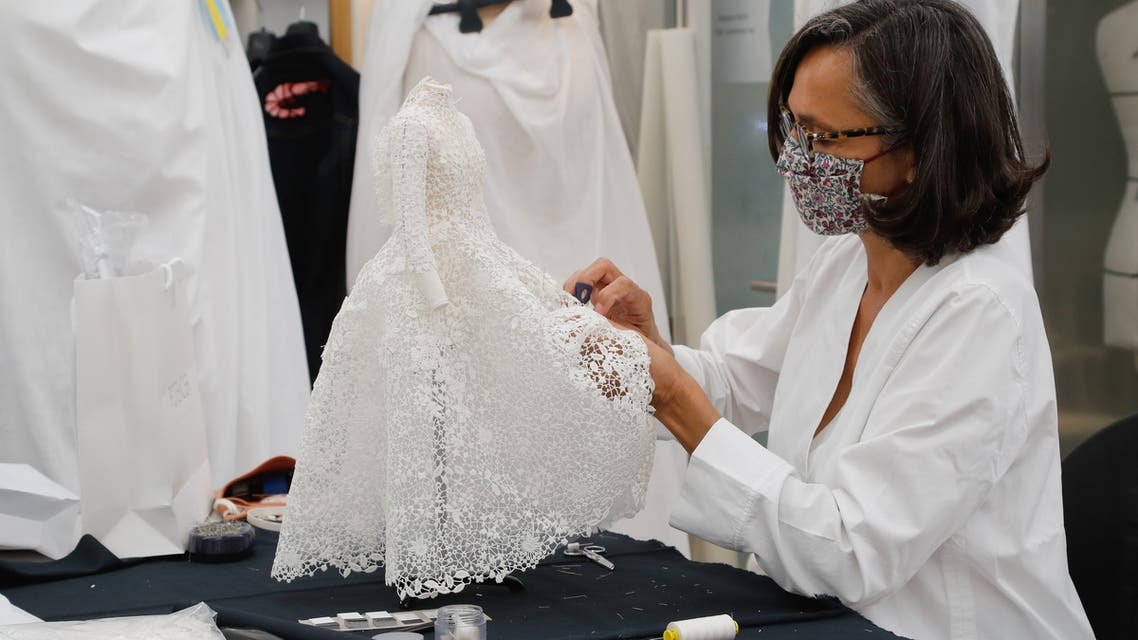 An employee sews a miniature dress for the recording of Dior Haute Couture collection's presentation movie, in Dior's sewing workshop in Paris, on July 4, 2020.