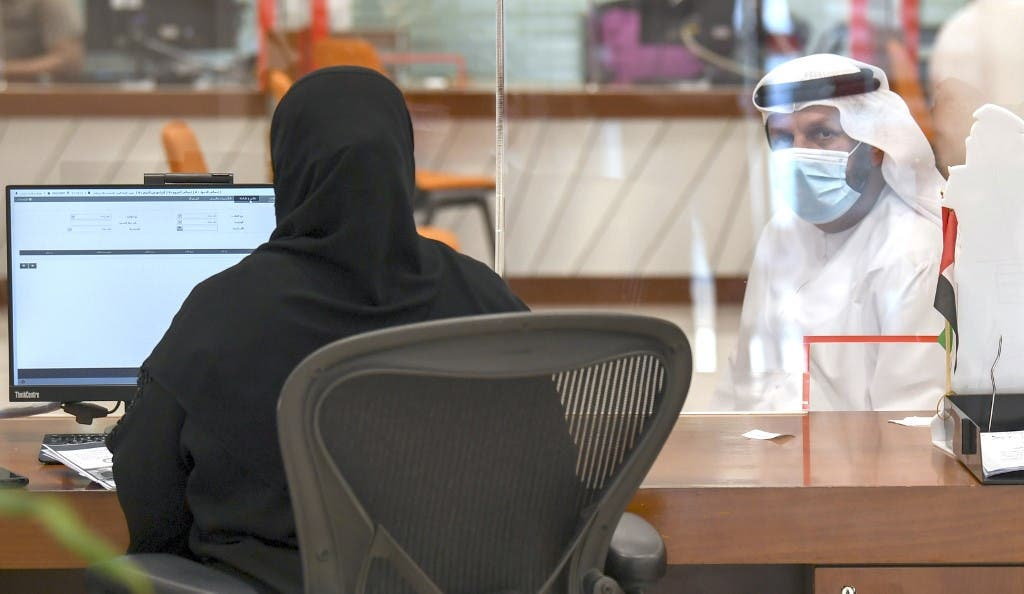 An Emirati civil employee tends to a visitor at the Passports Department as government employees return to work following the easing of restrictions in Dubai on 16 June, 2020. (AFP)