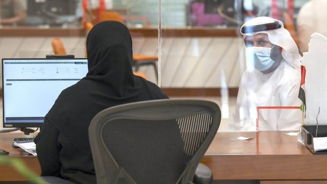 An Emiratia civil employee tends to a visitor at the Passports Department as government employees return to work following the easing of restrictions in Dubai on 16 June, 2020. (AFP)