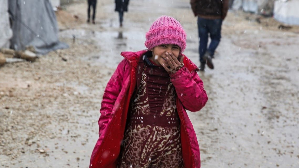 This handout photo released by Save The Children dated February 8, 2020 shows 9-year-old Syrian girl Zahira covering her face while walking amidst falling snow on a dirt path outside tents at a camp in the eastern countryside of Aleppo. (AFP)