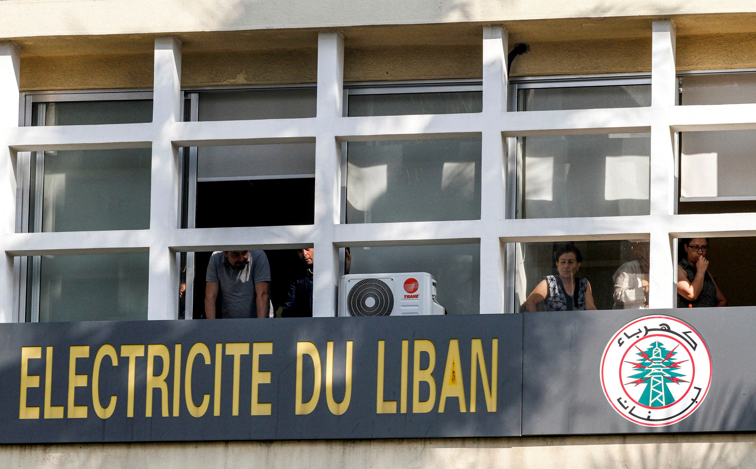Employees of the Electricite du Liban (Electricity Of Lebanon) national company look out of their windows at students gathering for an anti-government demonstration outside, in the southern city of Sidon on November 6, 2019. (AFP)