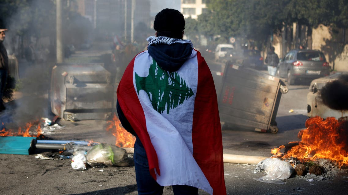(FILES) In this file photo taken on January 14, 2020, a Lebanese anti-government protester, wrapped in a national flag, stands in front of a road blocked with burning tyres and overtunrned garbage dumpsteres in Beirut. For months, Lebanon has grappled with its worst economic crisis since the 1975-1990 civil war.