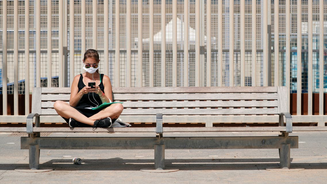 A woman sits on a bench near the Barceloneta beach after Catalonia's regional authorities decided to make mandatory the use of face masks in public at all times, during the outbreak of the coronavirus disease (COVID-19), in Barcelona, Spain July 9, 2020. (Reuters)