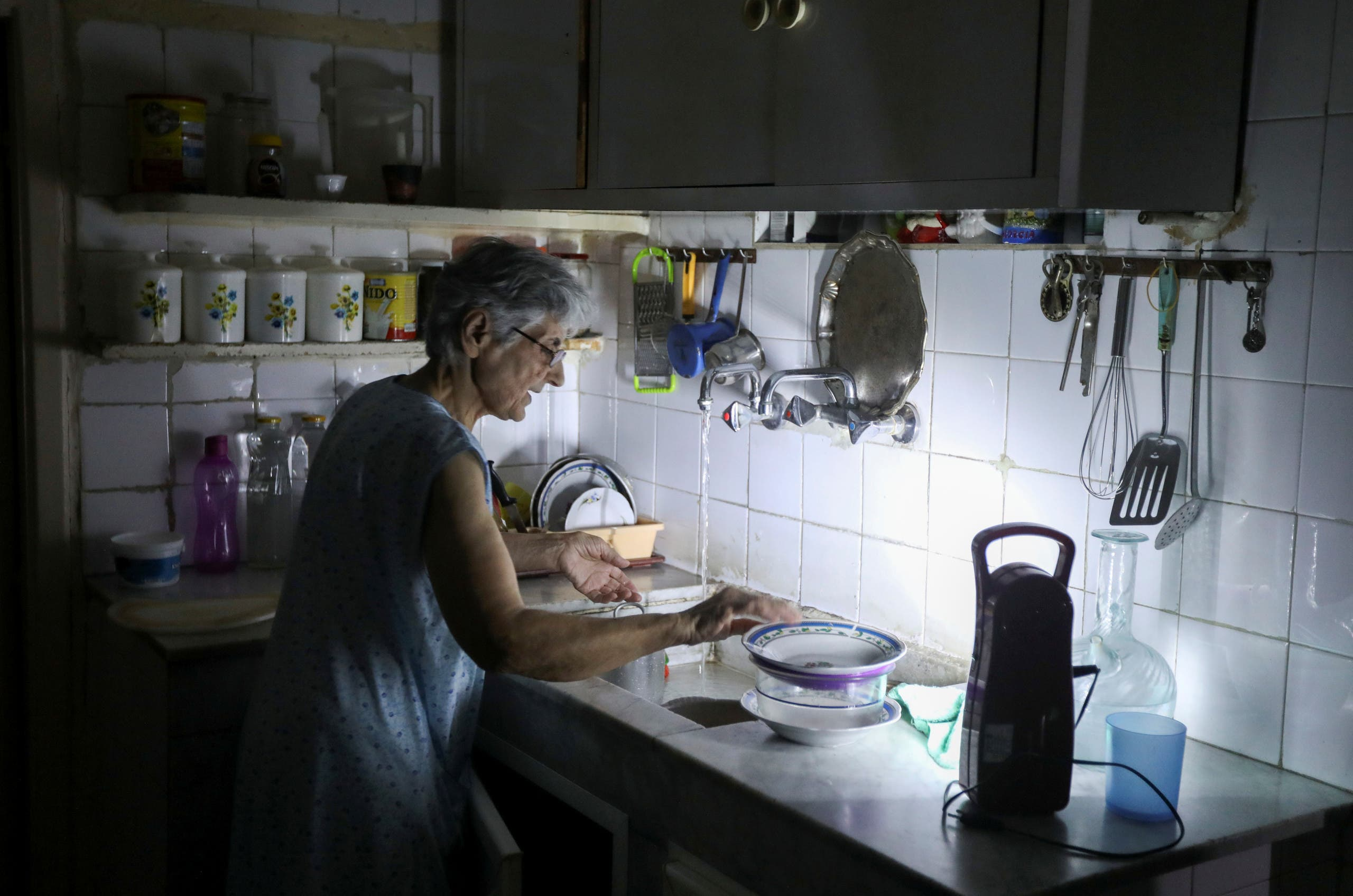Samira Hanna, 70, washes dishes in her kitchen as she uses a portable electric light due to a power cut, in Beirut, Lebanon July 6, 2020. Picture taken July 6, 2020. (Reuters)