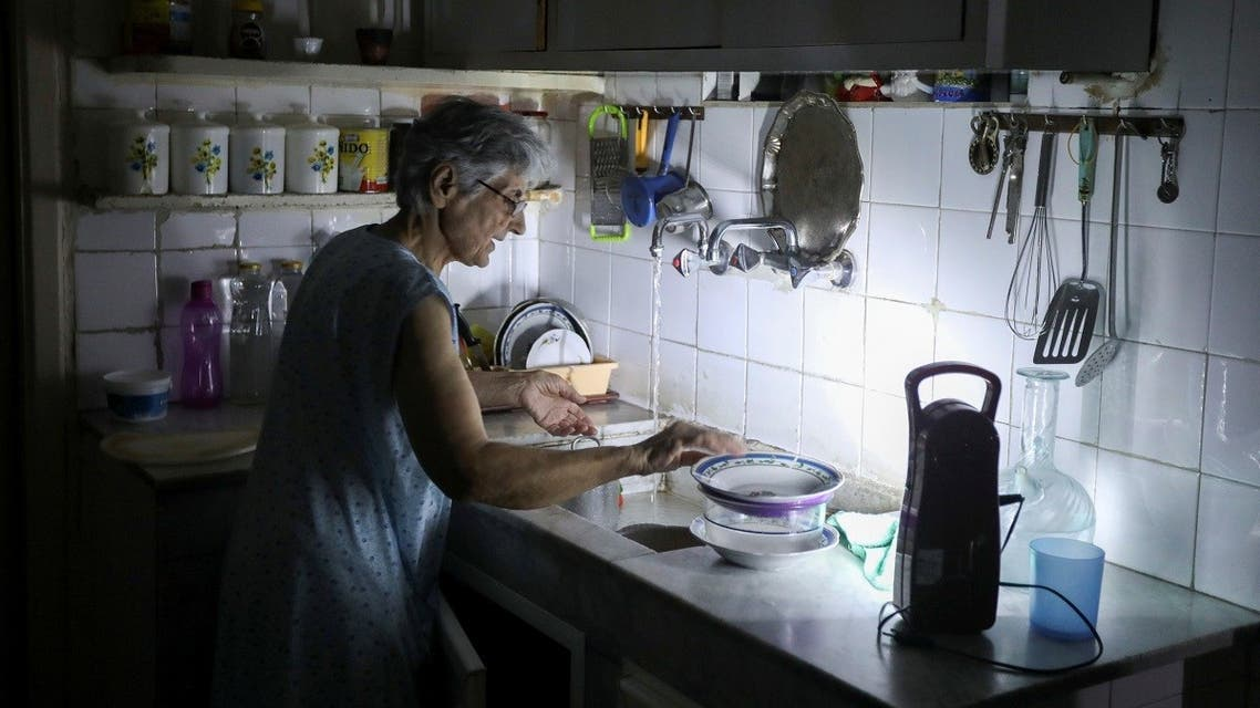 Samira Hanna, 70, washes dishes in her kitchen as she uses a portable electric light due to a power cut, in Beirut. (Reuters)