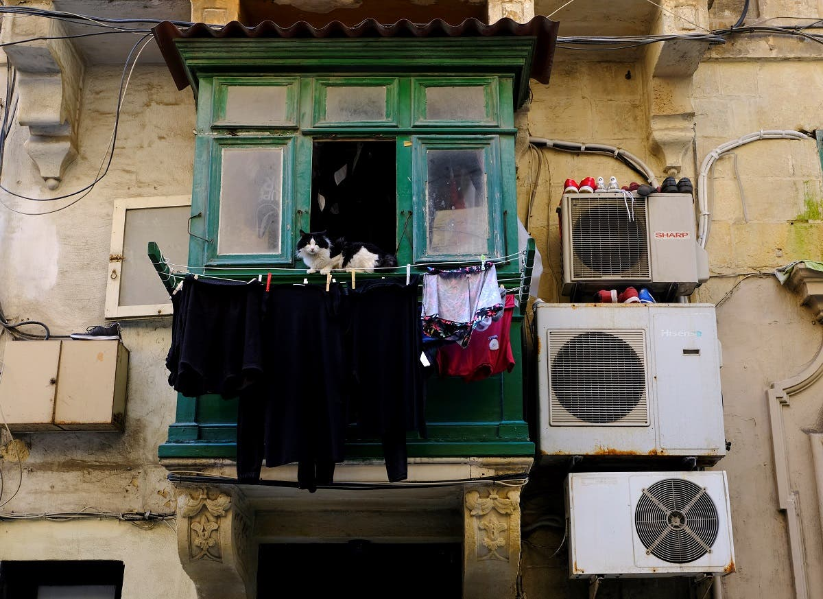 A cat sits in a balcony surrounded by hanging laundry and shoes on air conditioning units in Valletta. (Reuters)