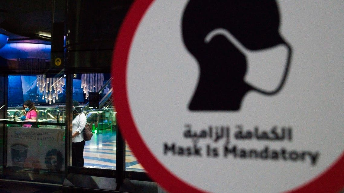 A commuter wearing a mask and disposable gloves due to the coronavirus pandemic waits for the driverless Metro at a station in Dubai. (AP)