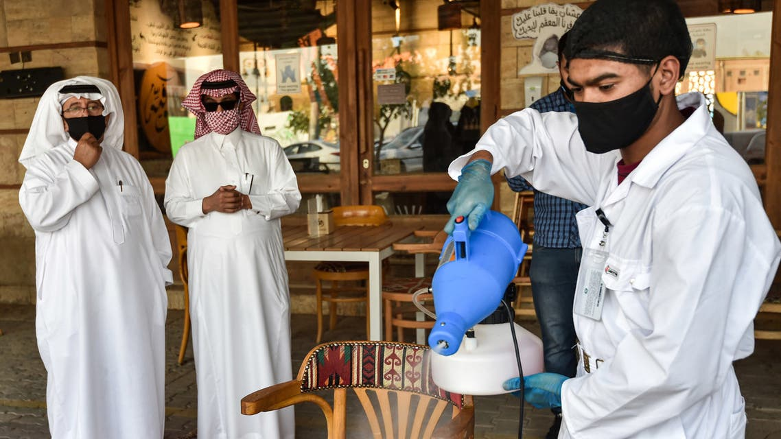 A latex glove-and-mask-clad worker sanitises a table for clients at a cafe in Saudi Arabia's capital Riyadh on June 21, 2020, as the country begins to re-open following the lifting of a lockdown due to the COVID-19 coronavirus pandemic.