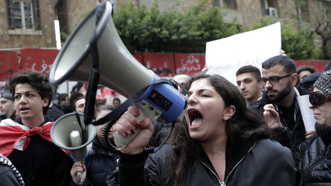 (FILES) In this file photo taken on December 30, 2019, a Lebanese anti-government demonstrator yells slogans as she takes part in a rally in front of the central bank building in the capital Beirut. For months, Lebanon has grappled with its worst economic crisis since the 1975-1990 civil war.