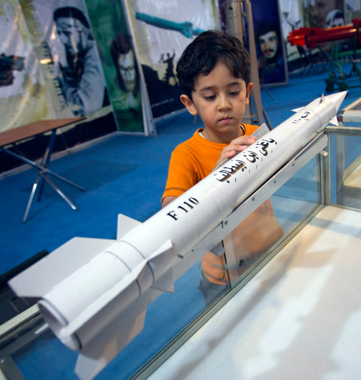 A boy looks at a model of an Iranian third-generation Fateh-110 surface-to-surface missile while visiting a war exhibition in south-eastern Tehran. (Reuters)