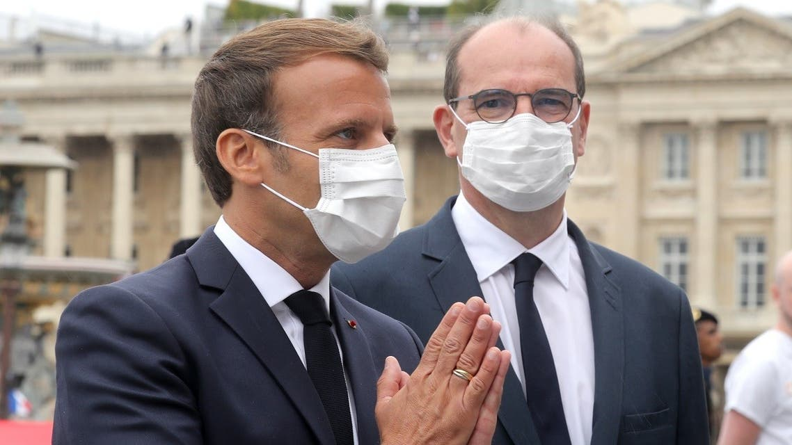 French President Emmanuel Macron (L) wearing a protective facemask greets guests flanked by French Prime Minister Jean Castex at the end of the annual Bastille Day military ceremony on the Place de la Concorde in Paris, on July 14, 2020. (AFP)