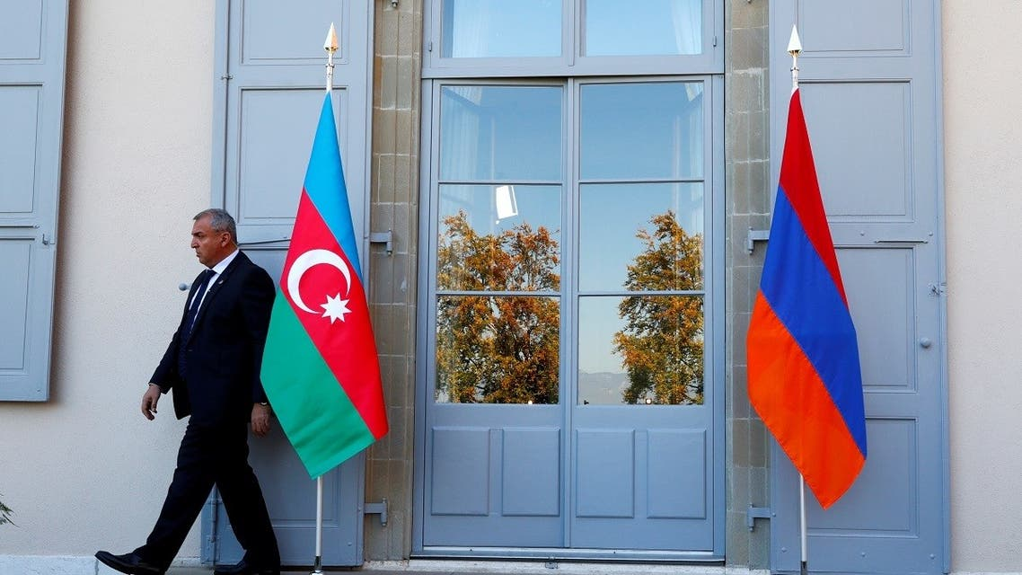 FILE PHOTO: A security guard walks past an Azeri (L) and Armenian flag at the opening of talks in Geneva, Switzerland, October 16, 2017. (Reuters)
