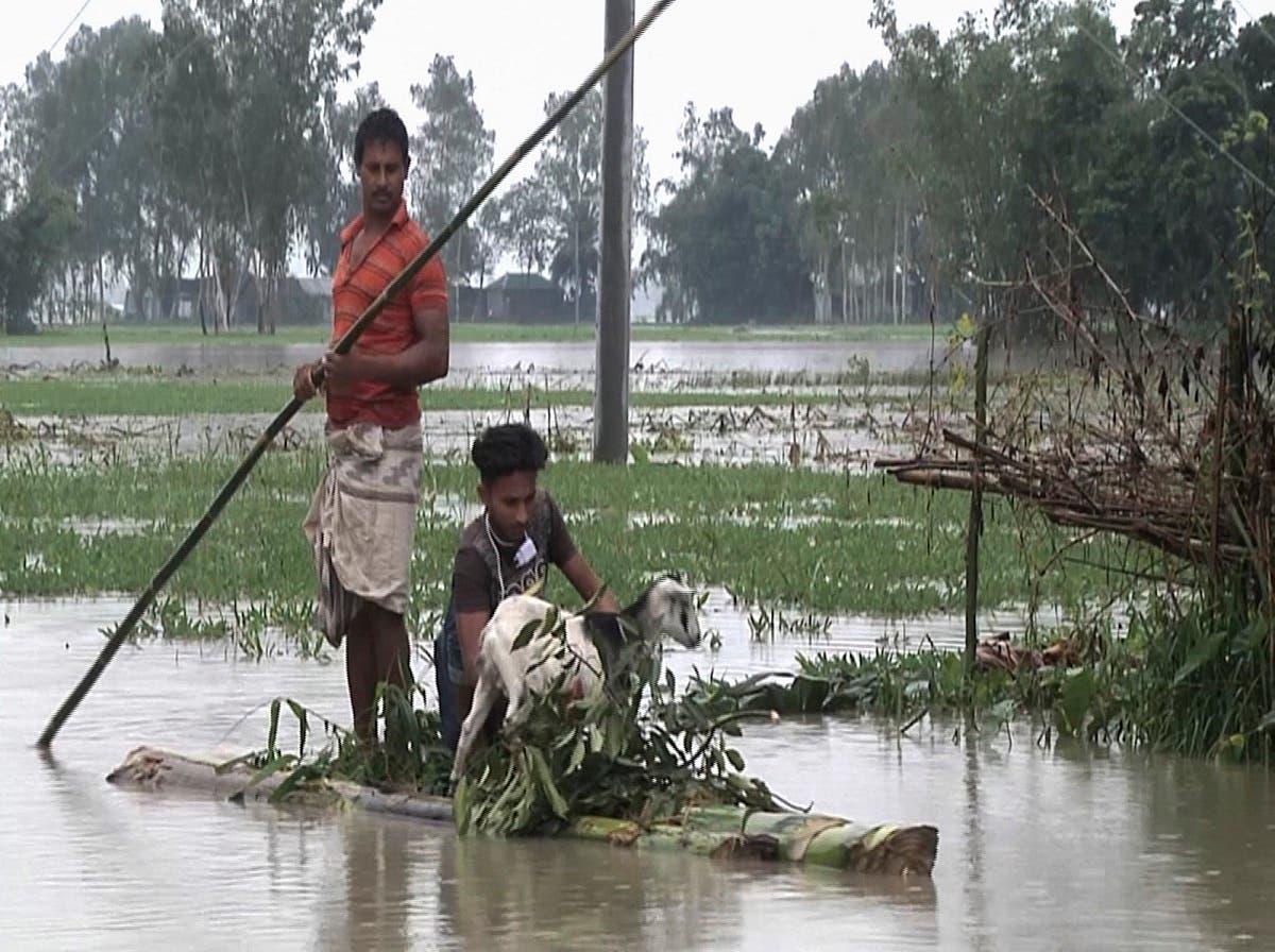 In this video grab  Bangladeshi men with a goat row a banana raft through flood waters in Lalmonirhat, Bangladesh, on July 13, 2020. (AP)